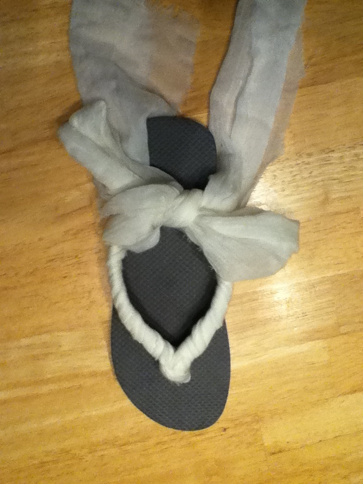 DIY fabric flip flops -take scarf , cut it the long way so you have two scarfs ( make sure it's a thin scarf) take one scarf , fold it the long way and loop around the thong of the flip flop. You will then have two strands of scarf on both sides of the flip flop. Do one side at a time and start wrapping around the flip flop. Hot glue when you get to the end. The left over scarf will tie up your leg.