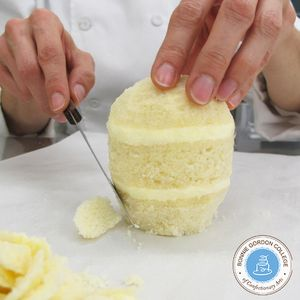 """Keep a flat, 1 1/2"""" wide base at the bottom as you carve the cake."""