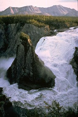 Virginia Falls, Nahanni NP Reserve, NW Territories  It has a total drop of 315 ft, making it about twice the height of Niagara Falls, and an average width of 850 ft. The rock in the center of the falls is called Mason's Rock, named after Bill Mason, the famous Canadian canoeist/ author/ filmmaker