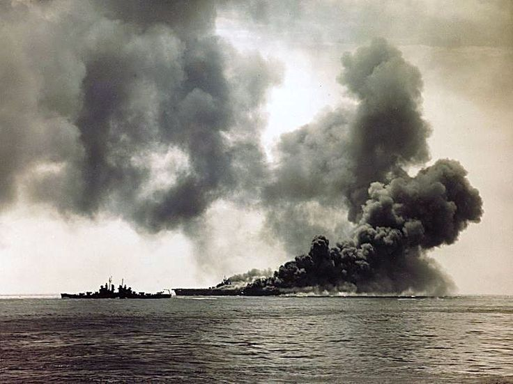 """USS Bunker Hill (CV-17) burning after being hit by a """"Kamikaze"""" off Okinawa, 11th May 1945. The Cleveland-class cruiser USS Pasadena (CL-65) is visible on the left"""