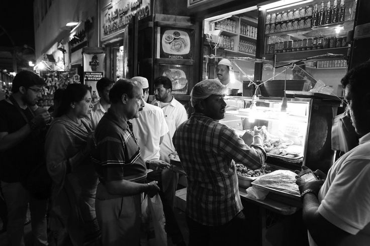 The queue for snacks at a Bur Dubai cafe.     A man stops for a think on a side street of Bur Dubai.     Cheap haircuts keep the customers rolling in.     Al Waqqas restaurant in Bur Dubai does a roaring trade.     Children's clothes on display in a shop.     Above, the work...