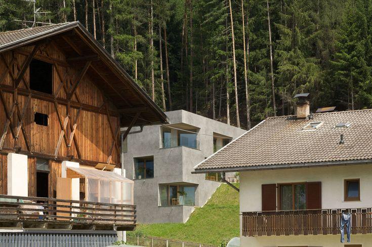 L'incarico consisteva nella progettazione di una casa con tre appartamenti, da inserire in un sito ripido alle pendici del bosco. Il risultato del processo di sviluppo progettuale è un monolite forato. La forma di base rimane quindi priva di finestre, una