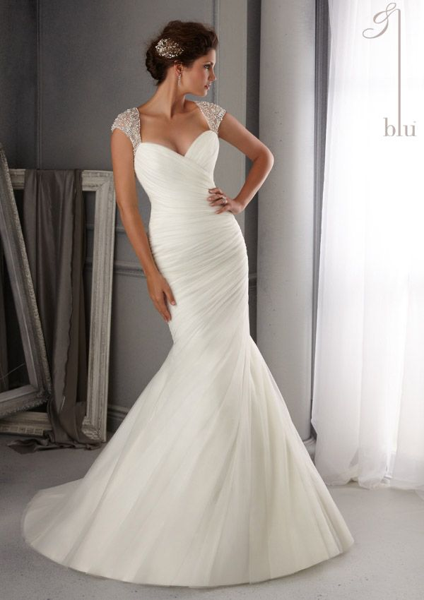 Intricate Crystal Beading Design forms the cap sleeve and illusion back of this soft net  mermaid style wedding dress. Available in white and ivory.