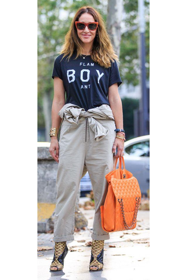 Un t-shirt imprimé retroussé dans un pantalon décontracté large avec des revers, un sac orange et des talons ouverts noirs et dorés.