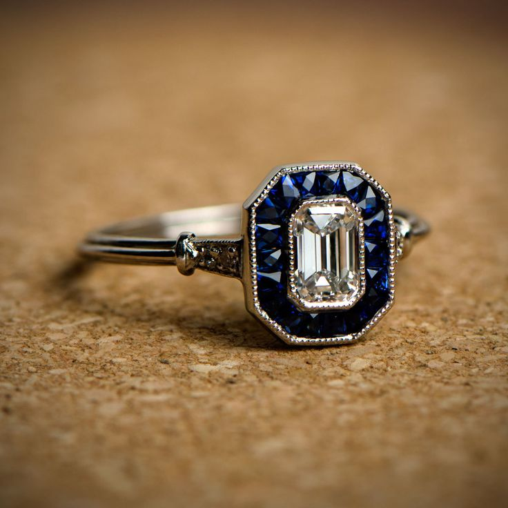 Diamond and Sapphire Engagement Ring, featuring a 0.60 carat emerald cut diamond and Celyon sapphires.