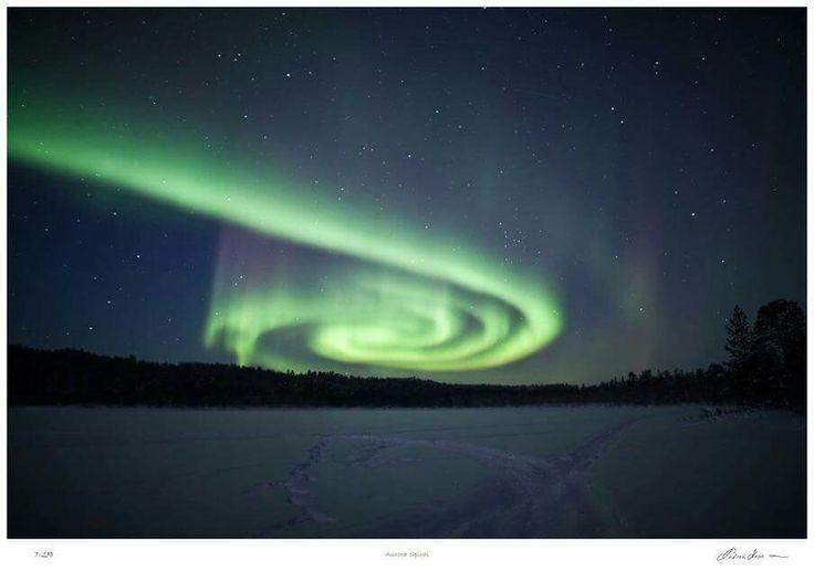 Autora Borealis forms a spiral shape over a frozen lake near Inari, Finland.