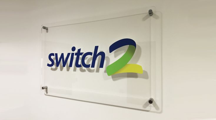 Switch2 Acrylic plaque installed into office entrance.  This simple signage transformed a blank wall into a more sophisticated inviting space. By Space3.co.uk