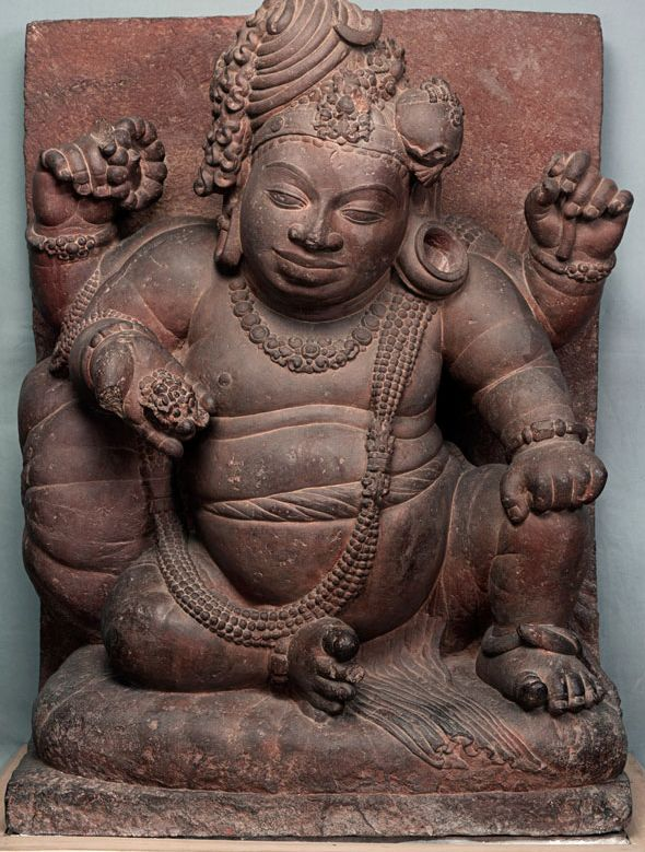 Shiva as Vamana (the corpulent dwarf). An image unlike most Shiva images. His 'jata-mukuta' is set on right side unlike the usual depiction of Shiva where the 'jata-mukuta', a central knot. His face indicates a jovial mood.   From Mansar, Nagpur, 5th century CE, Vakataka period.