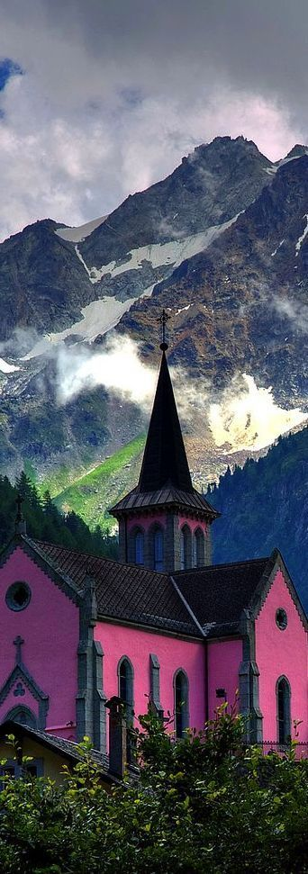 A pink church standing out with the Alps as its backdrop in Switzerland.