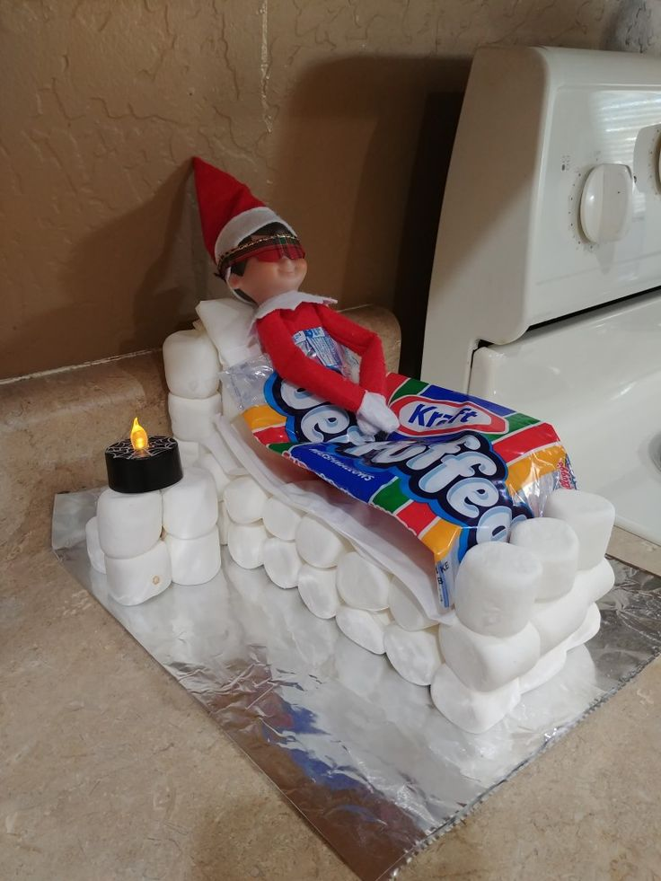 """Elf on the Shelf marshmallow bed. I just bought those too, Elvis! I used hot glue and toothpicks to assemble the bed and nightstand. His """"blanket"""" is a folded marshmallow bag. His """"sleep mask"""" is cut out from some Christmas ribbon. The kids really liked this one!"""