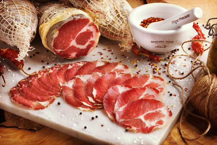 "Capocollo is a well marbled piece of meat. It is the continuation of the pork loin found under the shoulder blade and continues to the collar of the hog. Copocollo literally translates ""top of the neck"". When Niagara Food Specialties receives the shoulders, the cuts are trimmed and sea-salt preserved, then seasoned with a delicate pepper blend and air-dried for a minimum of 4 to 6 months before we bring them to market."