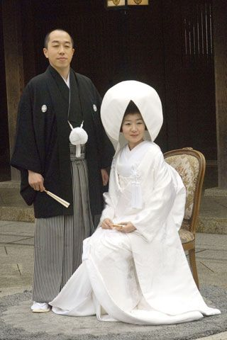 Bride and Groom in traditional wedding clothing, Japan. However, I can't say the white is probably very traditional. I assume that it is adopted from Western trends, since white, unlike black, is the color of dispair and death in most Asian cultures.