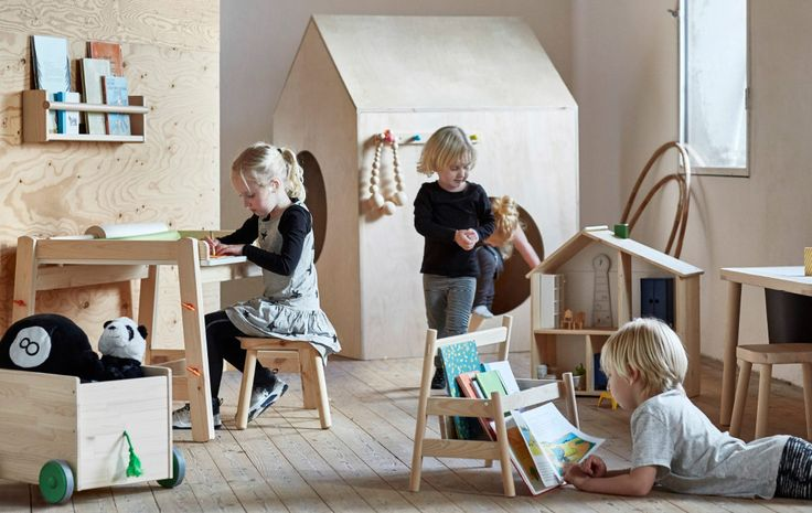 A display of a collection consisting of children's furniture such as desk, book display, stool, doll's house and a crate on wheels.