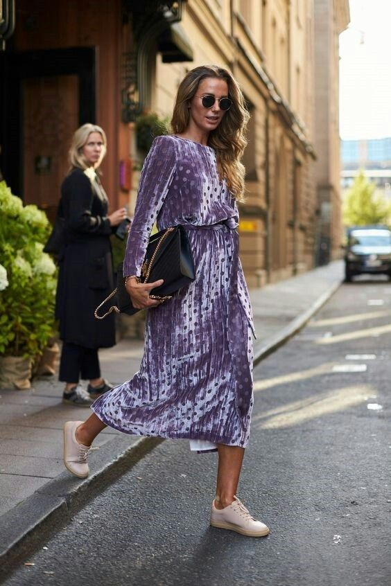 Velvet purple polka capri dress, chestlength honey hair, tan skin, blush sneakers; mustard masonry multistory façade