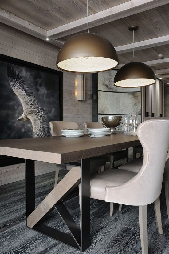 A dark, somewhat industrial dining area with dominant gold and black tones, plus a unique dark hardwood floor.