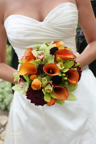 Orange, green, and burgundy bouquet featuring calla lilies, dahlias, and orchids.