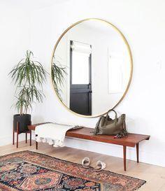 O branco preenche as paredes e é complementado pelo piso de madeira, o tapete persa, banco, vaso, e um enorme espelho redondo de moldura dourada