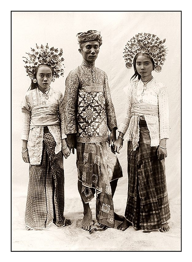 Two Balinese woman and a man. Date and photographer unknown.