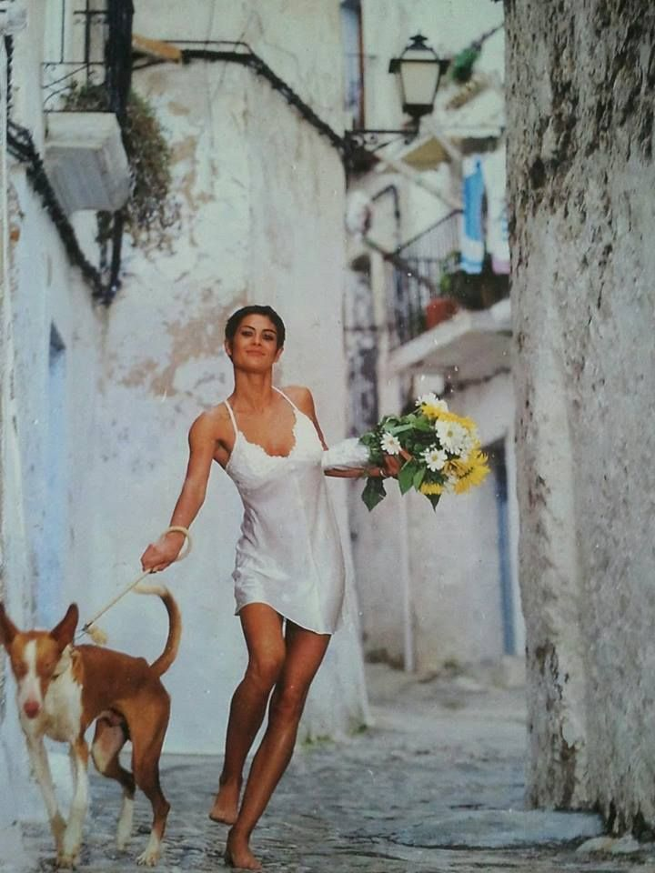 slinky white slip on dress flowers bouquet dog on a leash streets  dark brown hair bun