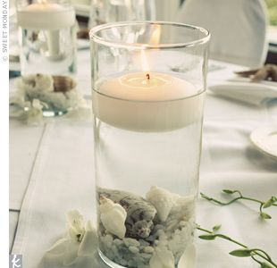 floating candles in vases filled with seashells and rocks added some