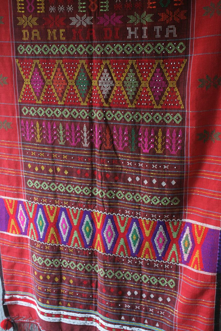 """Ulos is a very iconic textile of Batak people and regularly done with quite vary technique of weaving, tapestry, beadings and embellishment in one textile. This catchy one known as """"ulos sadum"""", a Toba sadum exactly, simply because it was made by a people of Batak Toba. New generation of sadum ulos woven with alphabetical pattern as a proof that the weaver isn't iliterate. This """"DAME MADI HITA"""" pattern, has the meaning of 'may peace be upon us"""". From Toba people in Medan, South Sumatera"""