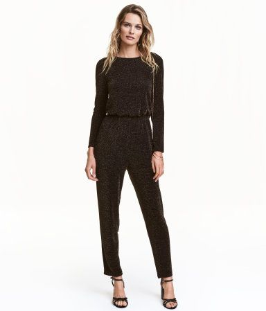 Black/gold-colored. Jumpsuit in glittery jersey. Draped neckline at back with cut-out section above waist. Long sleeves, elasticized seam at waist, and
