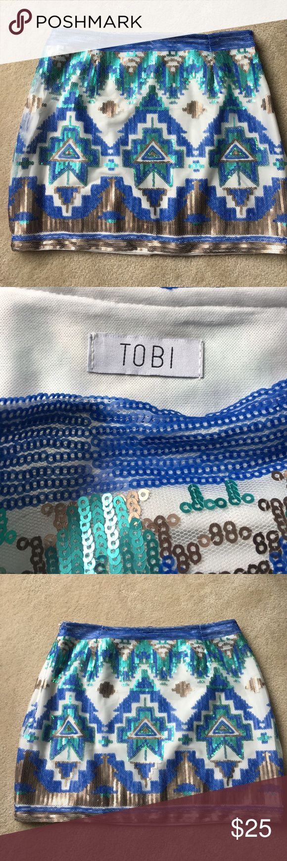 """Tobi Aztec blue, green, and gold sequin mini skirt Tobi blue, green, and gold/copper Aztec pattern sequin mini skirt.  Sequins are sewn onto a mesh fabric, which overlays white fabric underneath. Side zip closure with hook & eye clasp, but the eye needs sewn back down on one side. Otherwise excellent condition. Size tag says large, but length is 14"""", waist is 28"""". Tobi Skirts Mini"""