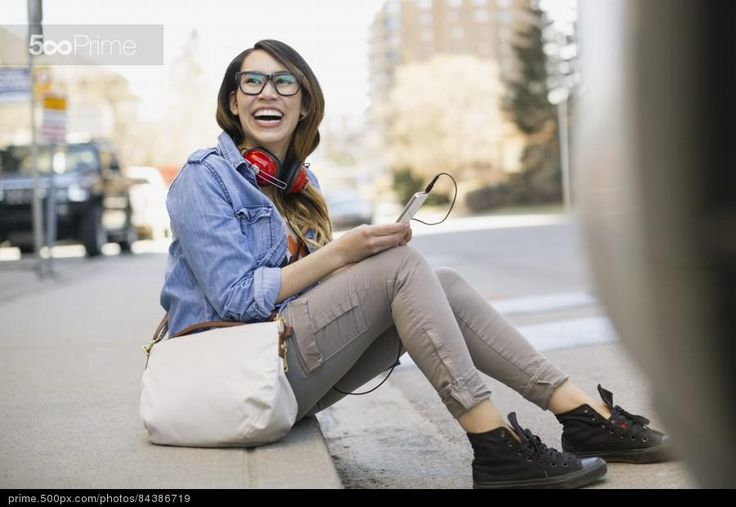 Woman with mp3 player laughing on urban curb by Hero Images | 500px Prime