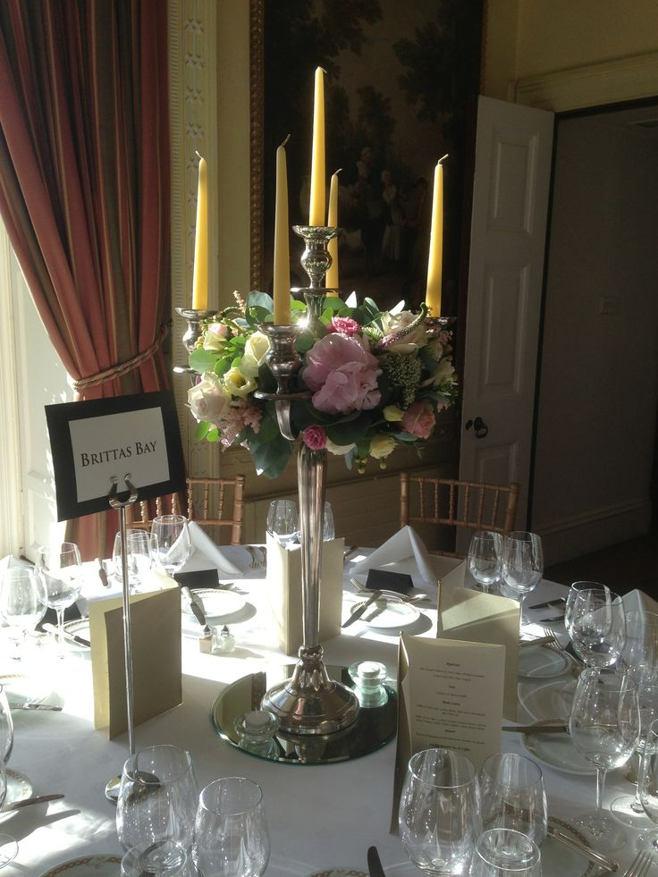 Table candelabra dressed with a ring of flowers including pink Hydrangea, cream Hypericum Berries, Roses, Trachelium, Lisianthus.