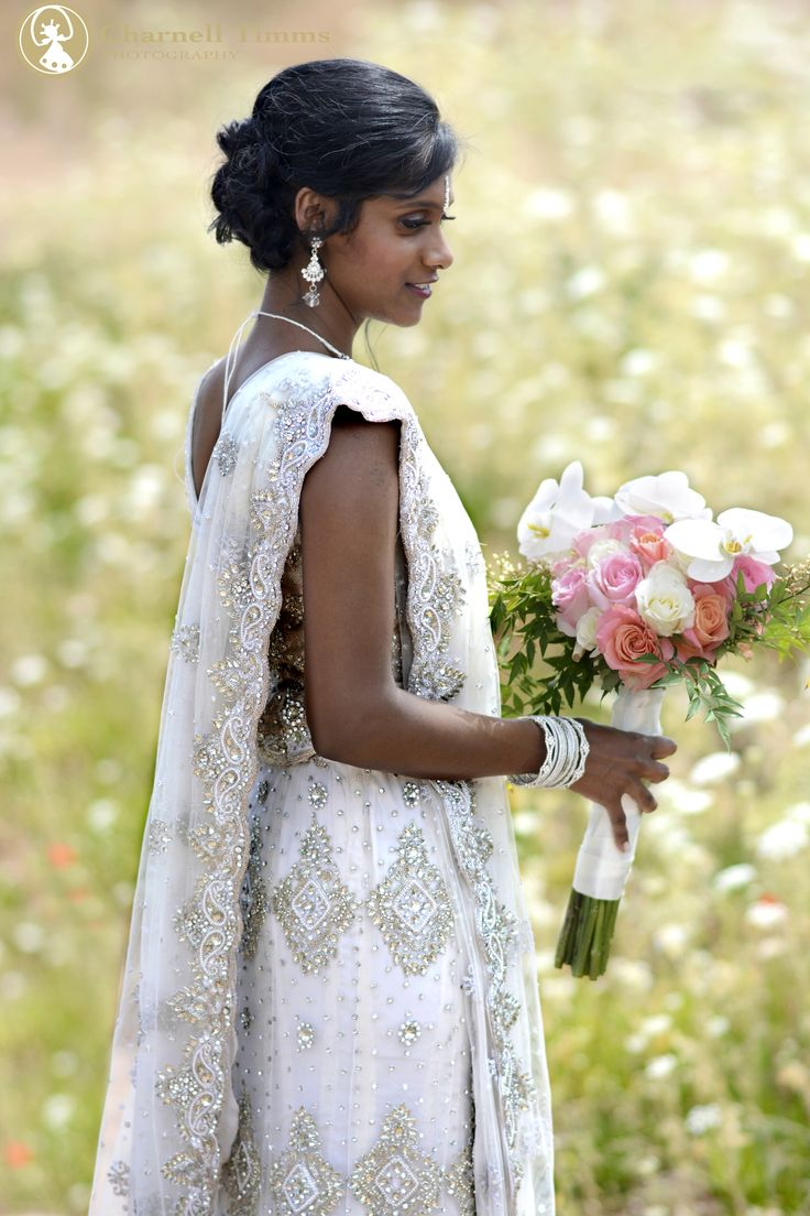 Derusha holding her bouquet in a field of flowers. Charnell Timms Photography