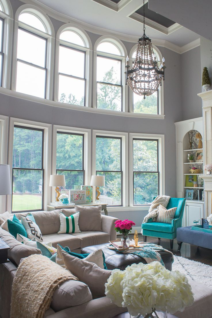 A traditional two story living room with gray walls becomes a show stopper  with vibrant pops