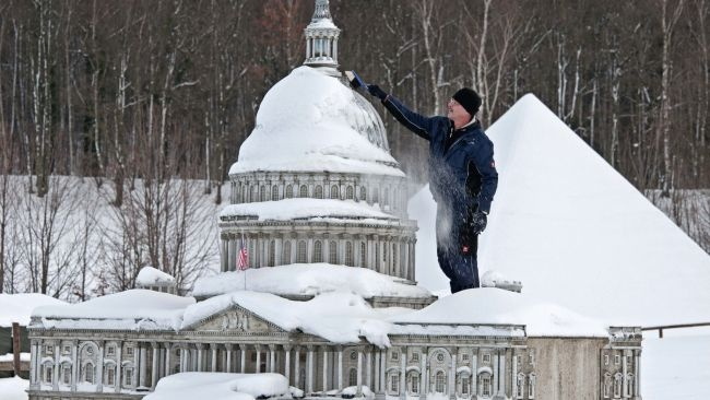 Capital Idea ~  Gunter Hersch cleans snow from the 1:25 scale model of the U.S. Capital in Washington at the Miniworld landscape park in Lichtenstein, Germany.  by Jens Meyer/AP Photo