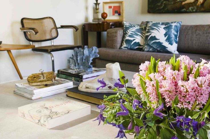 A flower arrangement of hyacinths and clematis on a low table in the a sitting room | Un arreglo de flores con clematis y jacintos en una mesa baja en el cuarto de estar