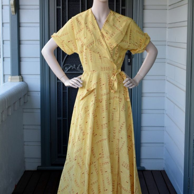 "Late 1940s Sunrise Housecoat on Velvet Rose's Pin Up Dressing Room Stunning full length yellow housecoat. Hollywood glamour, wrap dress. Made by ""Timely Fashions by More"" Muted yellow with a quirky brown spring print and lighter yellow shapes. Wrap style it has 2 internal hidden ties to hold it on place and one visible at the waist. Large shawl collar and short sleeves. Fitted bodice and waist with a softly flared skirt. Its sits and falls beautifully. My guess would be it is rayon. Full…"