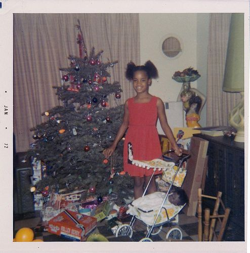 vintage christmas photo of a little girl and her new doll and doll stroller