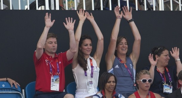"""Catherine, Duchess of Cambridge, takes part in a """"Mexican wave"""" with members of Team GB during the women's hockey bronze medal match between Britain and New Zealand at Riverbank Arena Hockey Centre during the London 2012 Olympic Games August 10, 2012."""