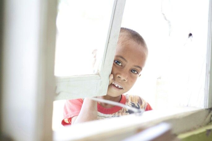 A young boy trying to learn through the window as he can not afford to attend school.