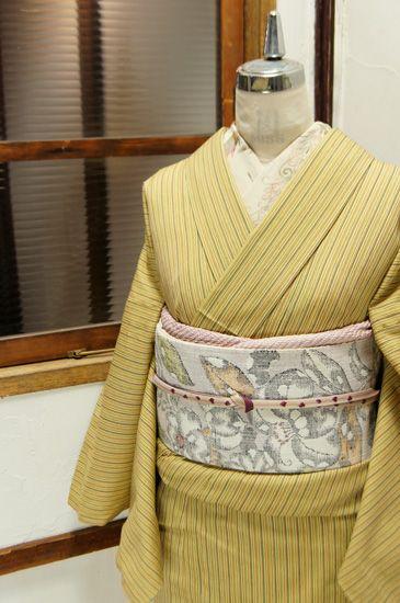 たまご色を基調にやわらかな色合いで織り出された縞模様がモダンなウールの単着物です。