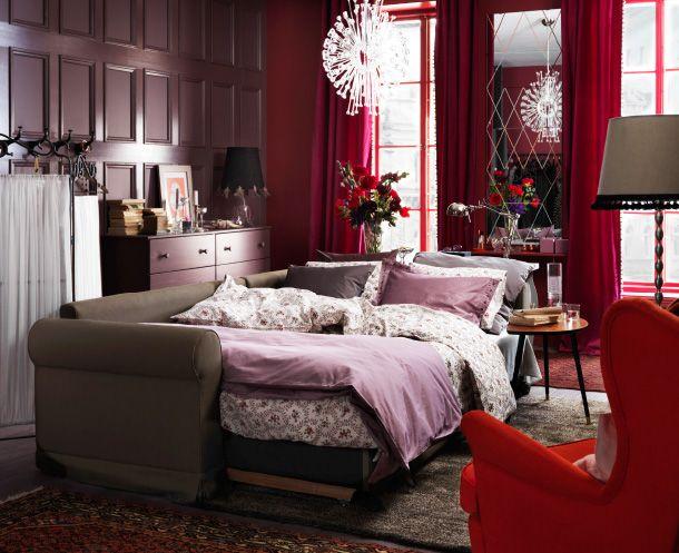 レッドとパープルでデコレーションしたリビングルームで、ソファベッドをベッドとして使用。