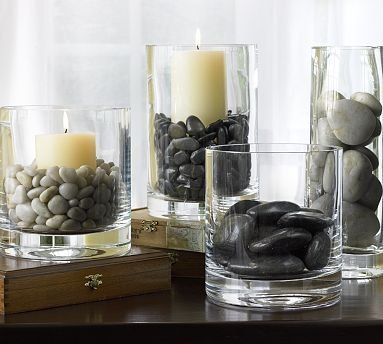 Use river rocks to anchor pillar candles, or set them in the bottom of clear vases for a more dramatic flower display. Source