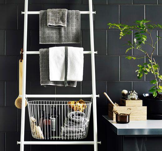 Biały wieszak na ręczniki w kształcie drabiny z koszem oraz szarymi ręcznikami, oparty o ścianę z szarymi płytkami.