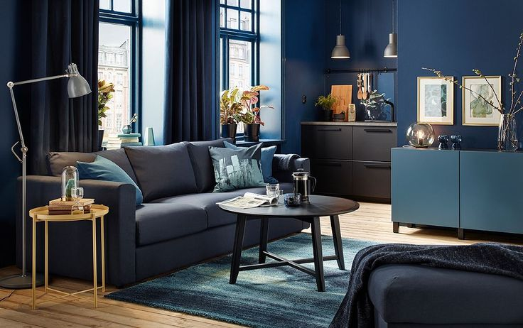 Small dark blue living room with black-blue sofa and black round coffee table.