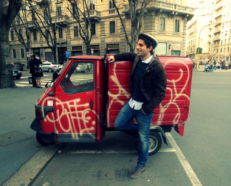 """""""ApeCar SuperStar"""": Omar in una posa plastica e per nulla forzata in tenuta casual con coppola e ApeCar rossa. Corso Magenta."""
