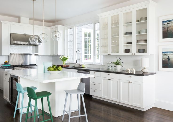 For a young family's Northern California home, designer Mead Quin stuck to tradition with a blissfully white kitchen, adding green and blue stools around the island for color. To create extra space for storing and displaying beloved tablewares, Quin incorporated glass-front cabinetry above the kitchen's counters. | archdigest.com