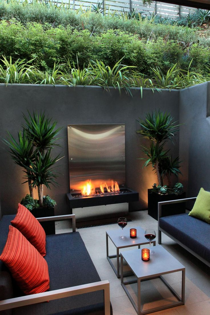 This sunken patio is surrounded by gray concrete walls and lush vertical landscaping, creating a private, intimate atmosphere. Sleek, contemporary sofas make a cozy seating area in front of a stainless steel floating fireplace.