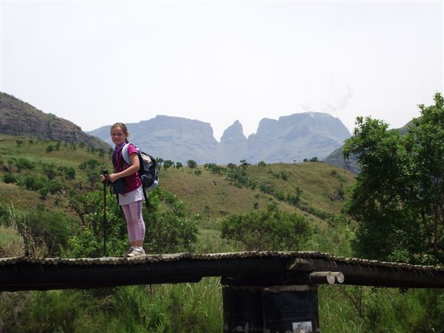 www.gohiking.co.za Mishy on the bridge over the Delmhlwazini River - Champagne Castle, Monk's Cowl and Cathkin Peak in the background