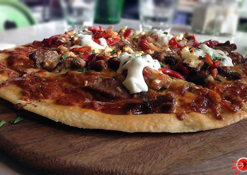 Marinated Lamb Gourmet Pizza – With capsicum, spanish onion, feta, oregano, on a garlic olive oil base splashed with tzatziki & mozzarella