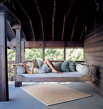 Oversized porch swing on wood-paneled porch
