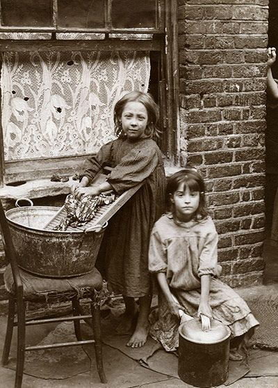Fascinating book of photos of Spitalfields/London street kids. Credit: Horace Warner/The Religious Society of Friends in Britain Two girls wash clothes in the street