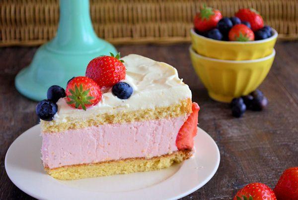 Verse aardbeien kwarktaart tussen twee lagen biscuit. Met een topping van mascarpone crème en verse aardbeien en bosbessen is deze taart niet te weerstaan.